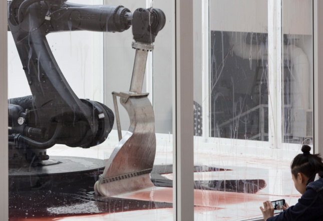 A robot arm with a squeegee end sweeping at a red liquid on the floor