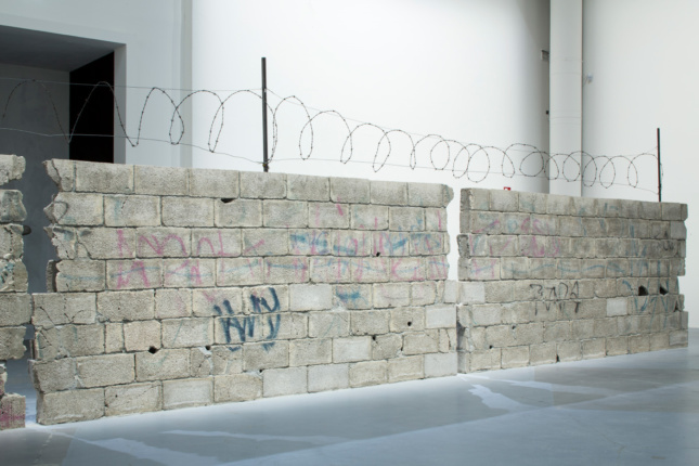 A 39-foot-long concrete block wall topped with razor wire