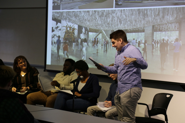 Photo of student standing up alongside panel of peers reading script