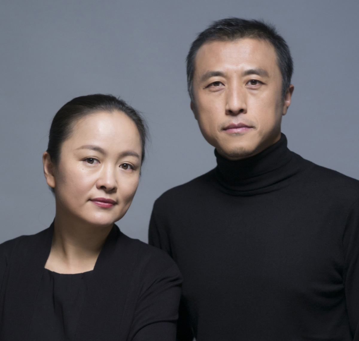 An Asian man and woman in black next to each other