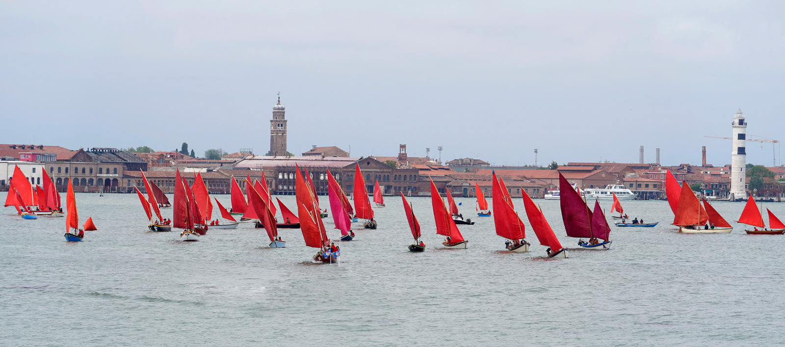 A fleet of red sailboats on a canal