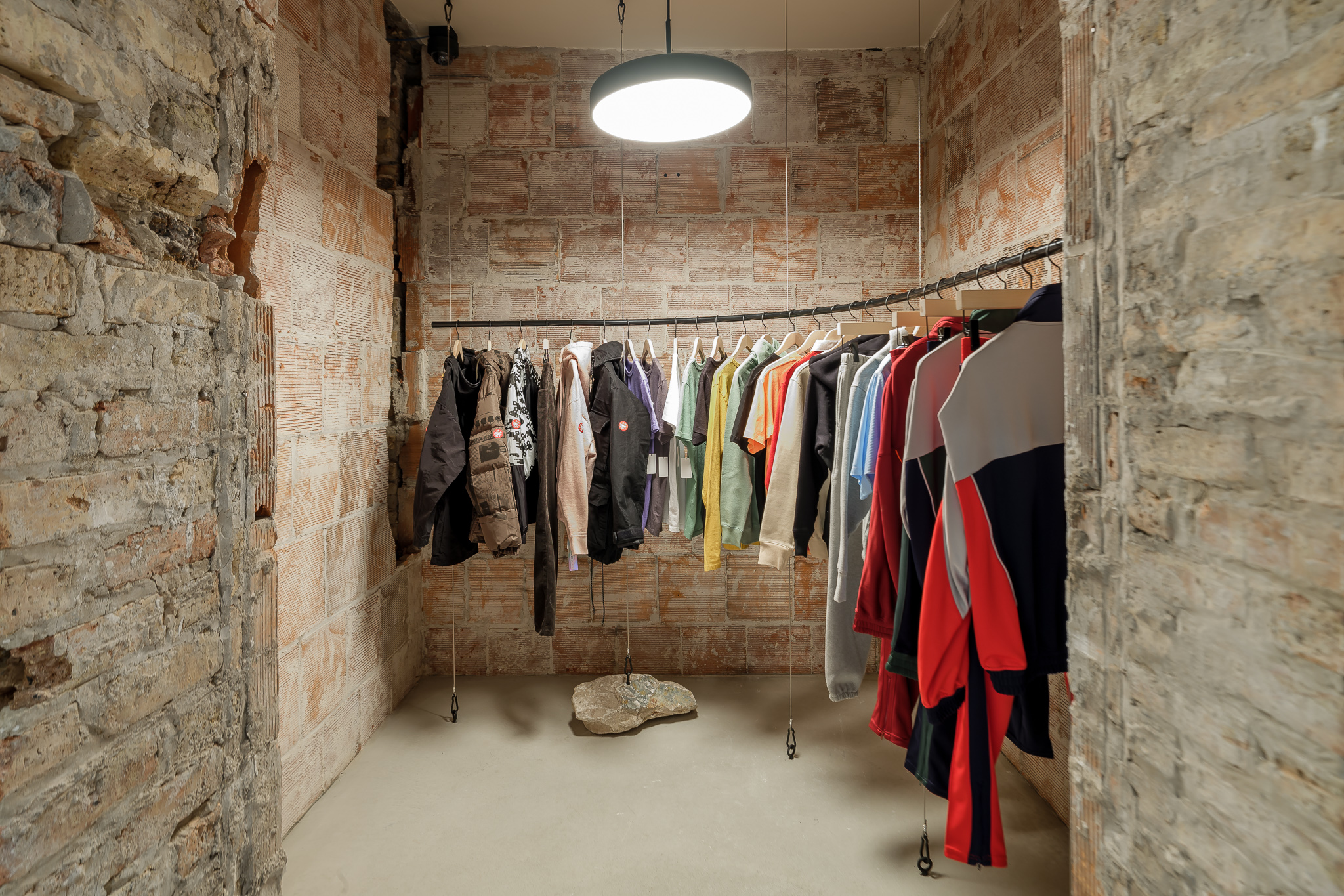 Photo of clothes hanging in room with unfinished stone and brick walls