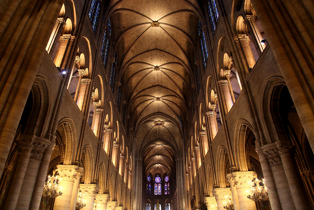 Image of inside Notre Dame cathedral with candle lit vaults and columns