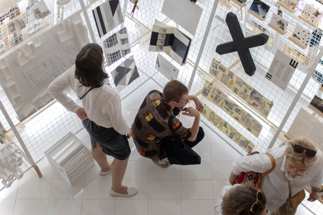 Aerial view of students looking at installation with X symbol displayed