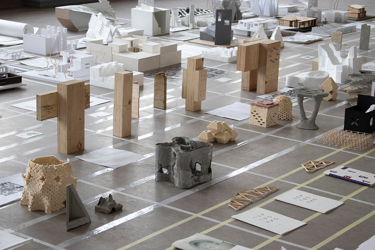 Close up image of artifacts made from wood and concrete displayed on floor in a grid