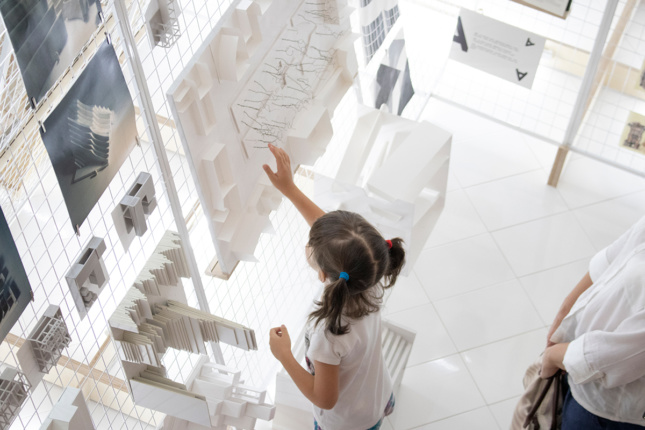 Aerial view of little girl touching a white exhibition installation mounted on wire scaffolding