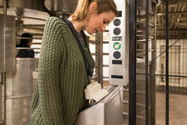 Photo of woman next to a turnstile, using a lanyard to swipe into the card reader