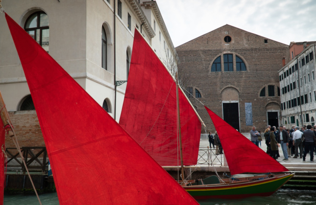 Red sailboats docked in front of a brick building