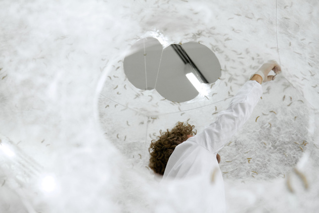 Photo looking up at woman (Neri Oxman) touching the inside of a white, woven pavilion full of silkworms
