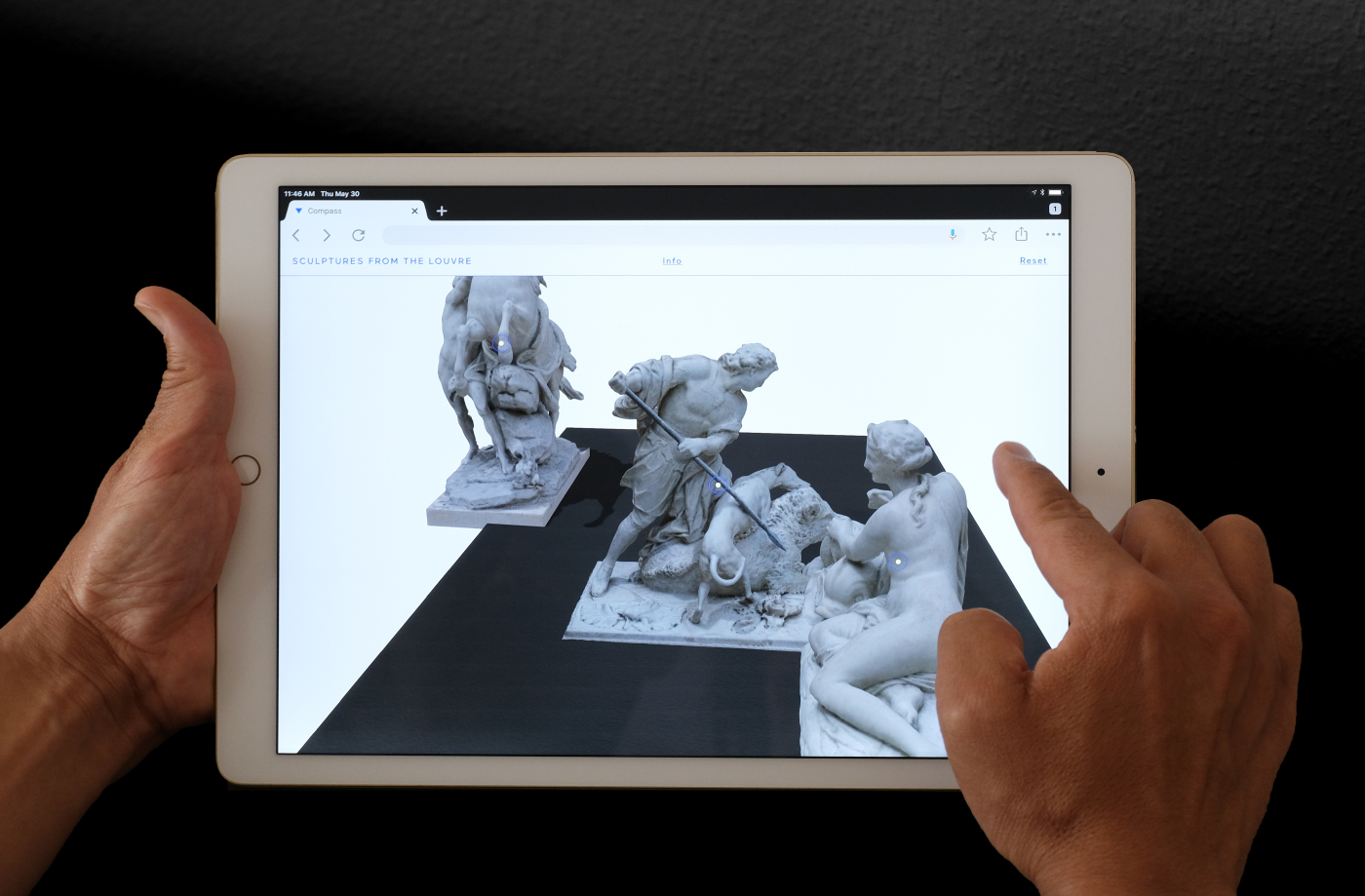 An iPad displaying figurative sculptures which are being dragged around.