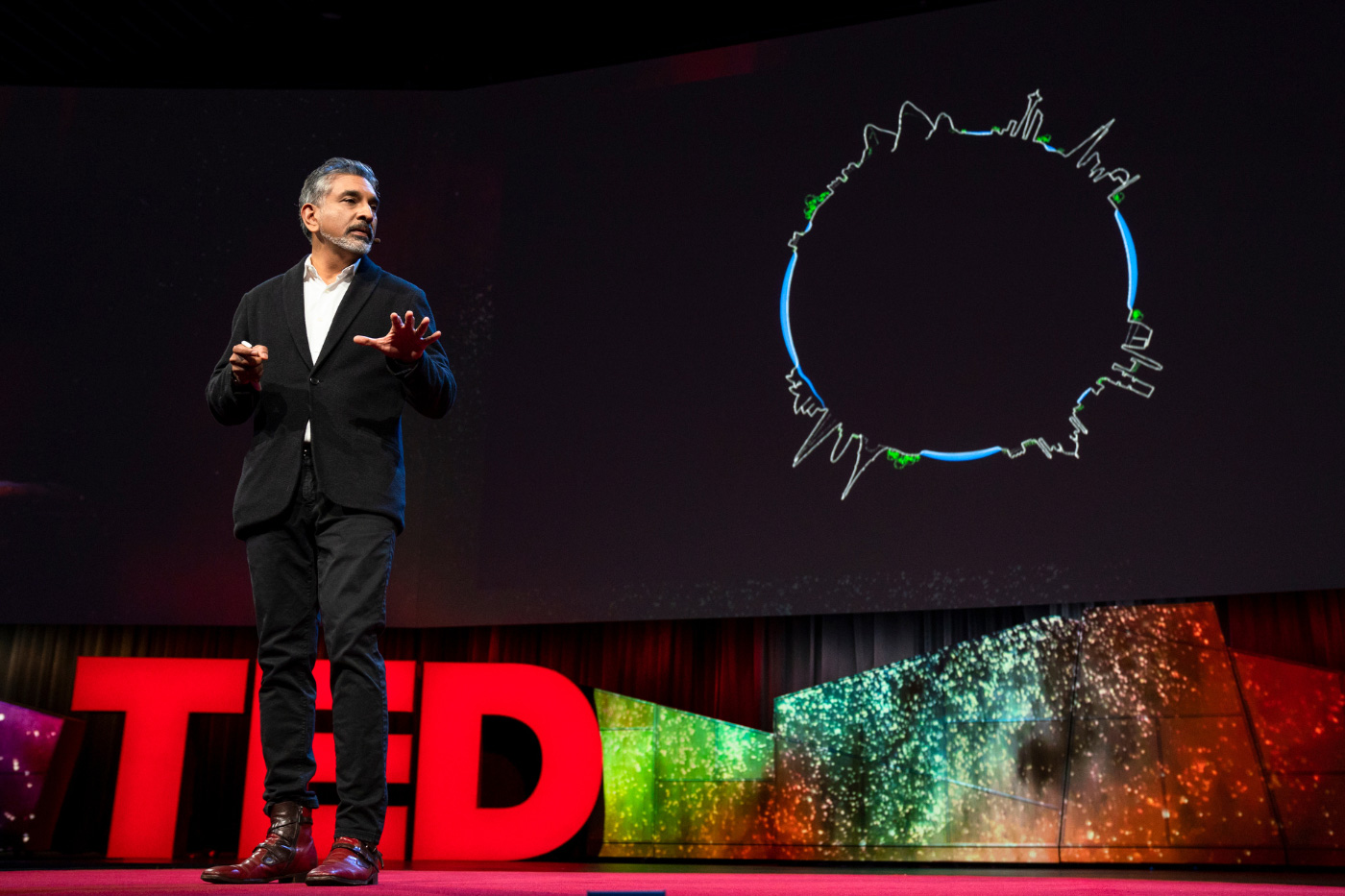 An indian man in a black suit on a stage, with the letters TED in large text