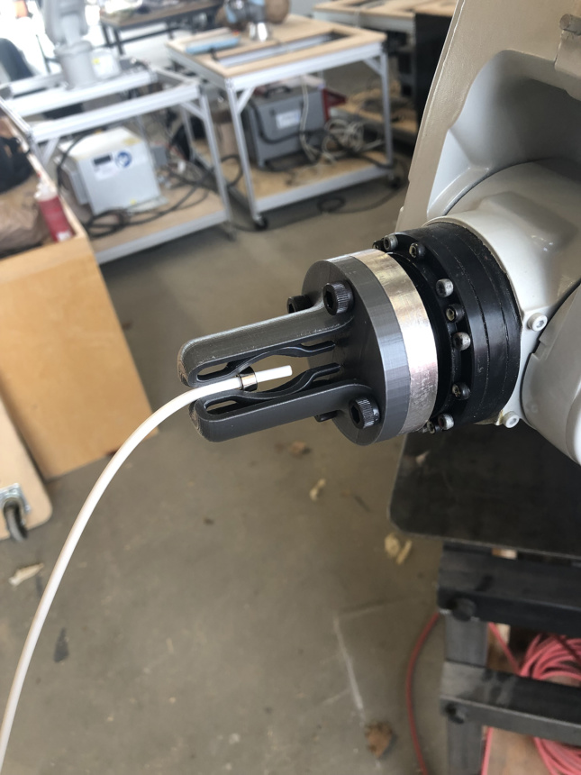 A close up of a robotic arm with a plastic grip holding a rope