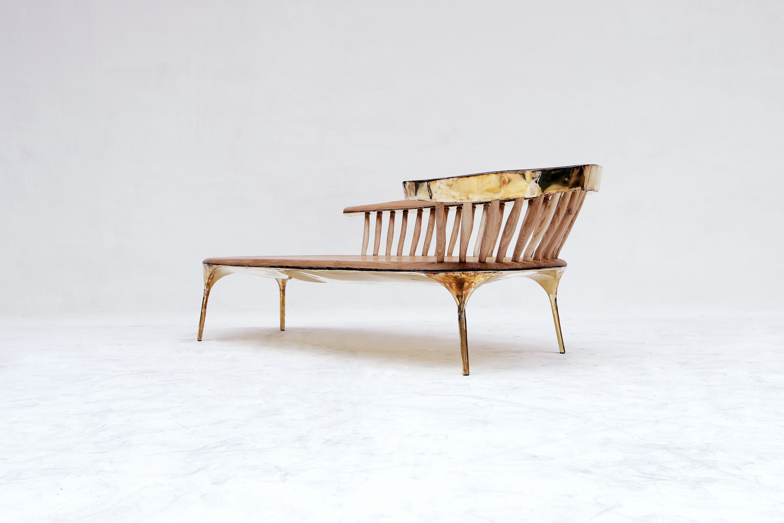 A bench with brass backing and wood seating