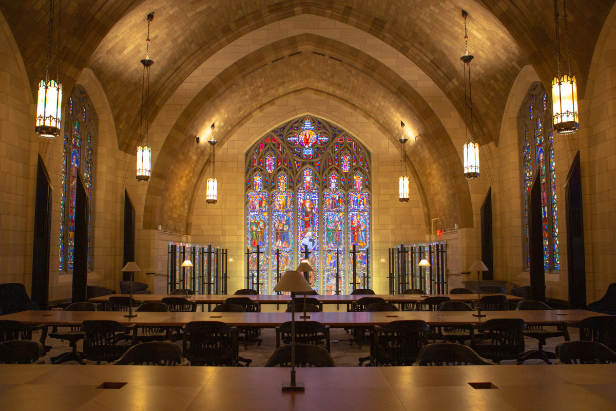A stained glass window in front of a row of workstations