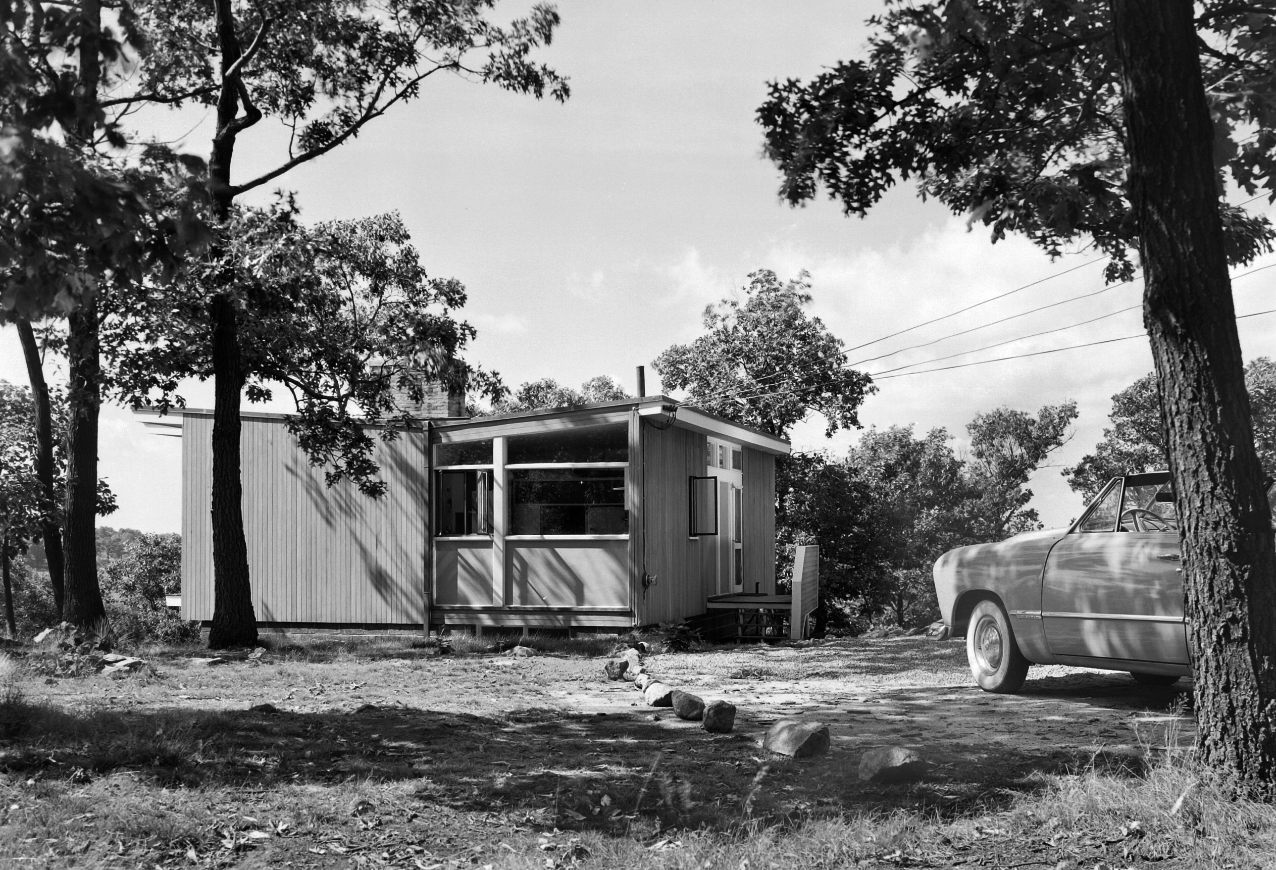 Black and white photo of a small house with a car in front