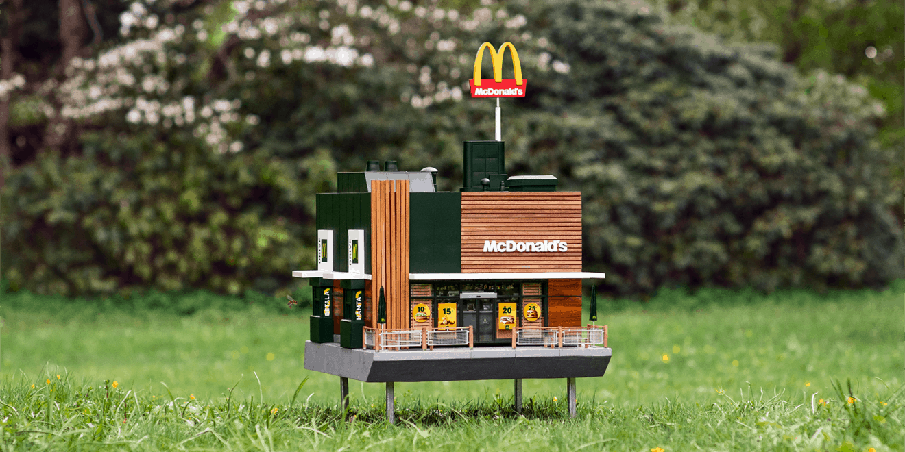 Photo of tiny McDonald's restaurant model sitting in a field