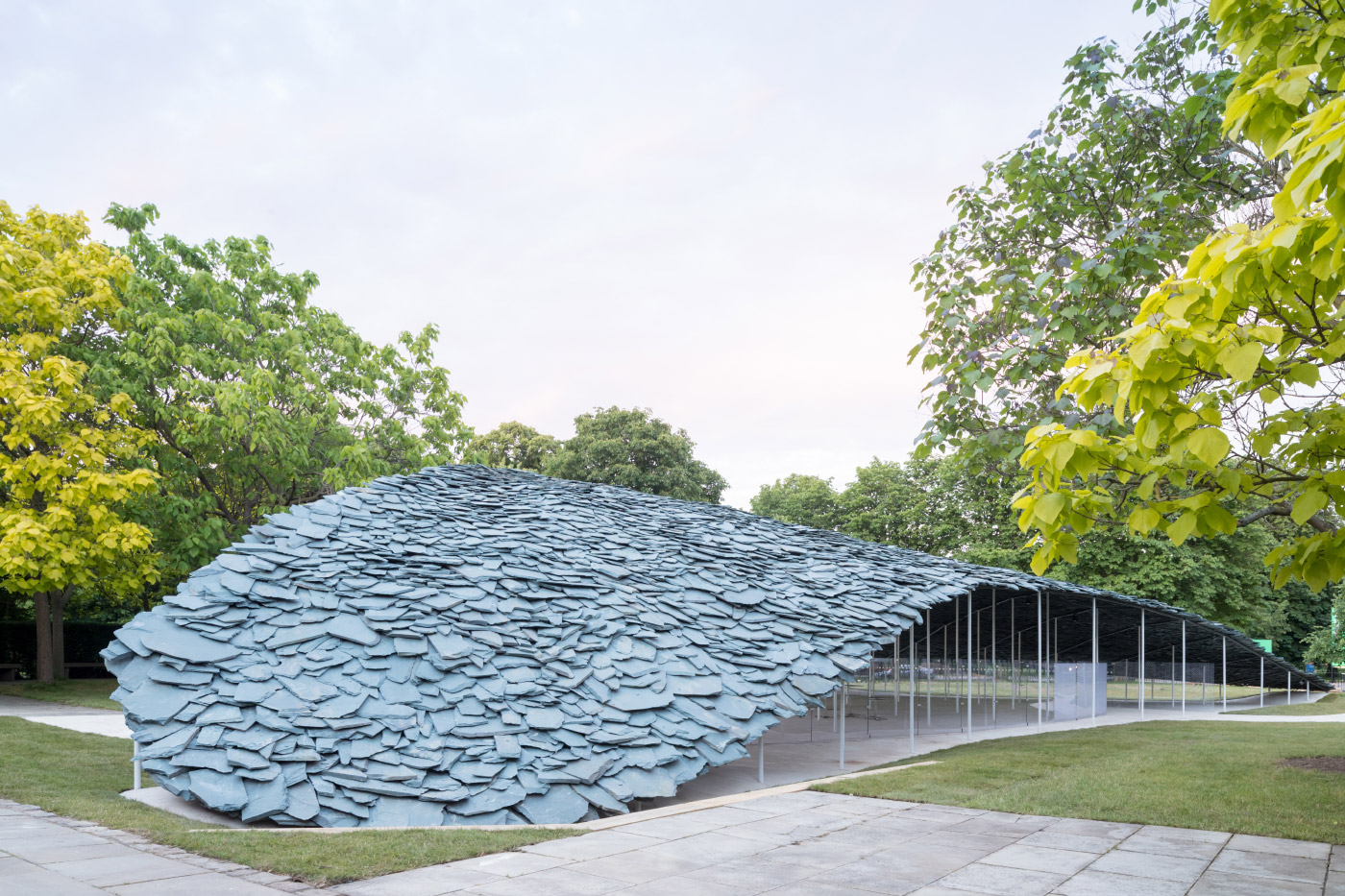 Photo of the 2019 Serpentine Pavilion, a low-slung building covered in slate tiles