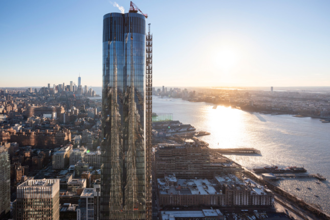 A glass tower rising on the Hudson River