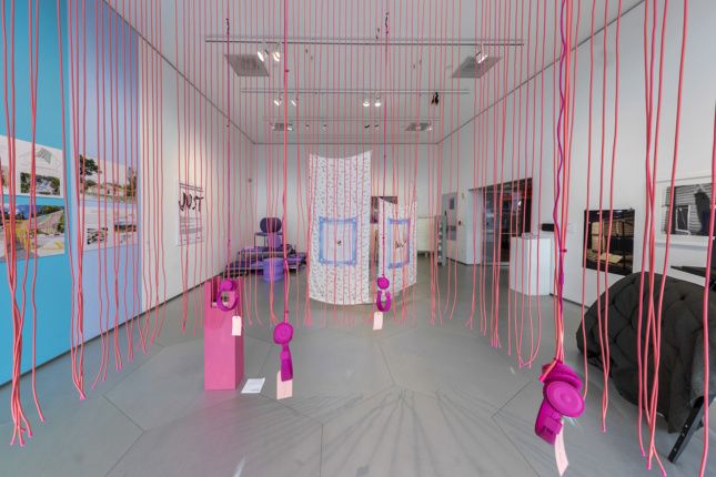 Interior of an exhibition with pink string suspended from the ceiling