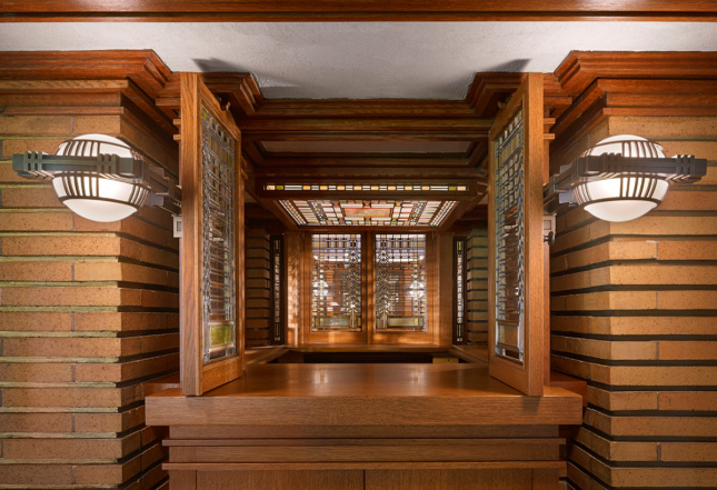 Intricate glasswork in a doorframe flanked by two lights at the Martin House