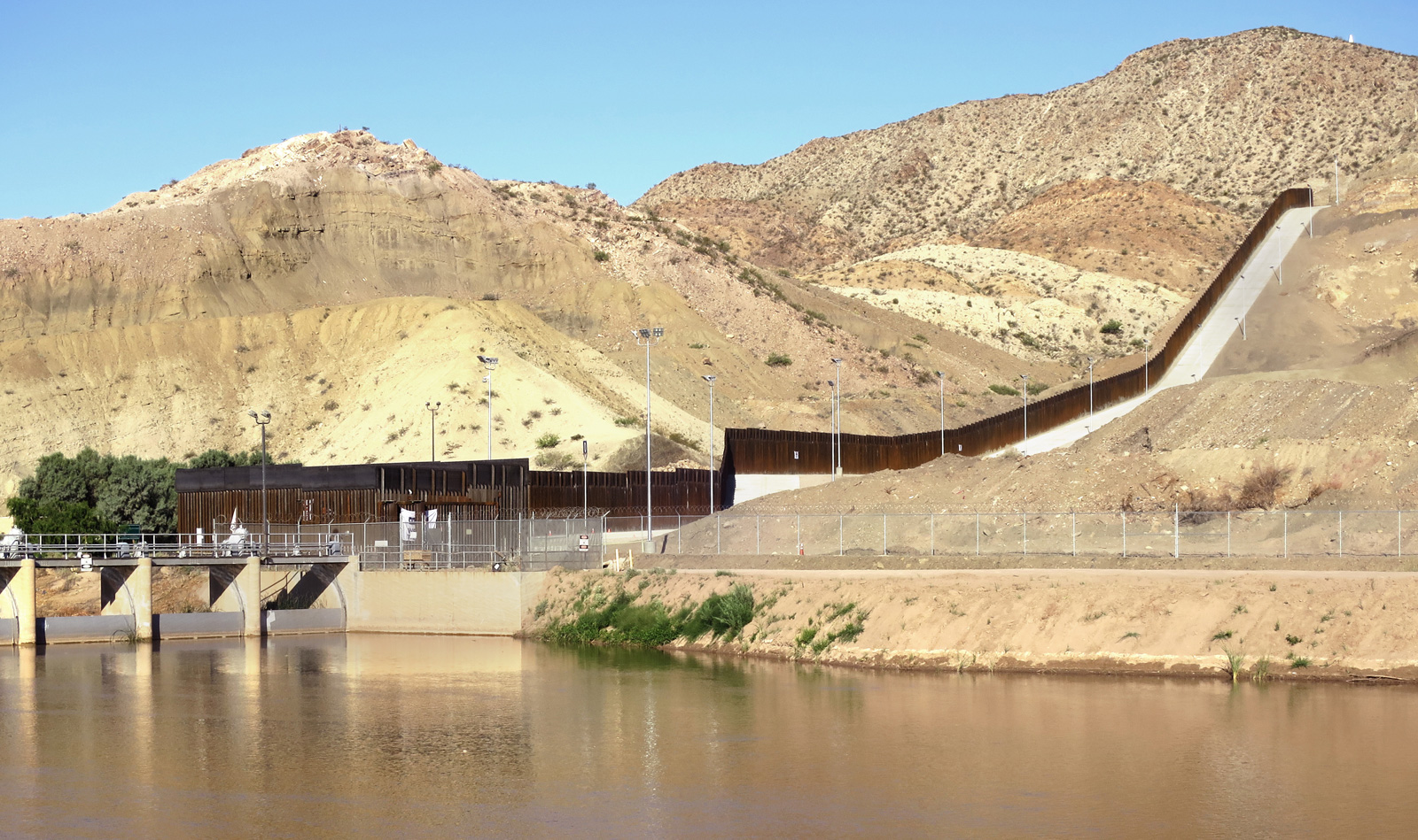A border wall running along hills and a river in Texas