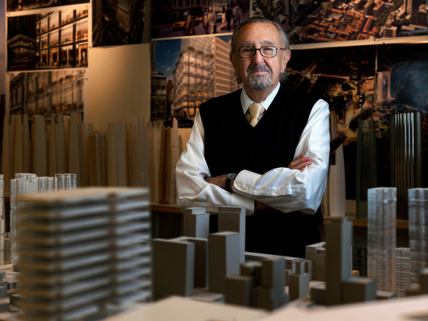 An older man, César Pelli, standing among building models