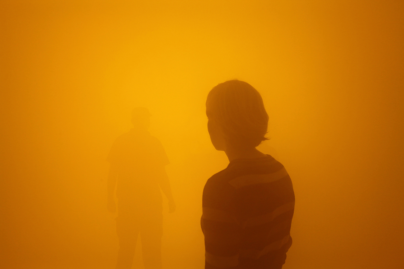 Two people wandering through an orange fog, at the Olafur Eliasson Tate show