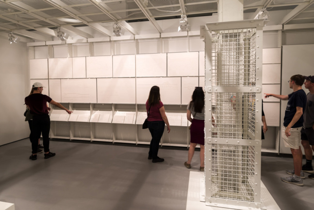 Installation view of several young people looking at wall of plaster, rectangular casts and a gas column
