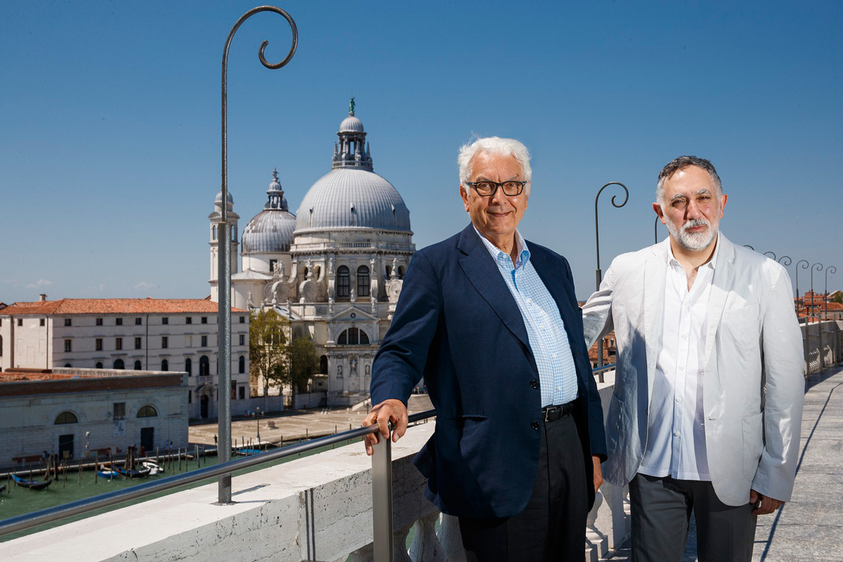 Photo of two men standing on bridge, in announcement for the 2020 Venice Architecture Biennale