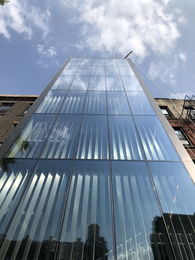 The rear of 277 Mott Street, a monumental glass curtain wall covering a stairwell