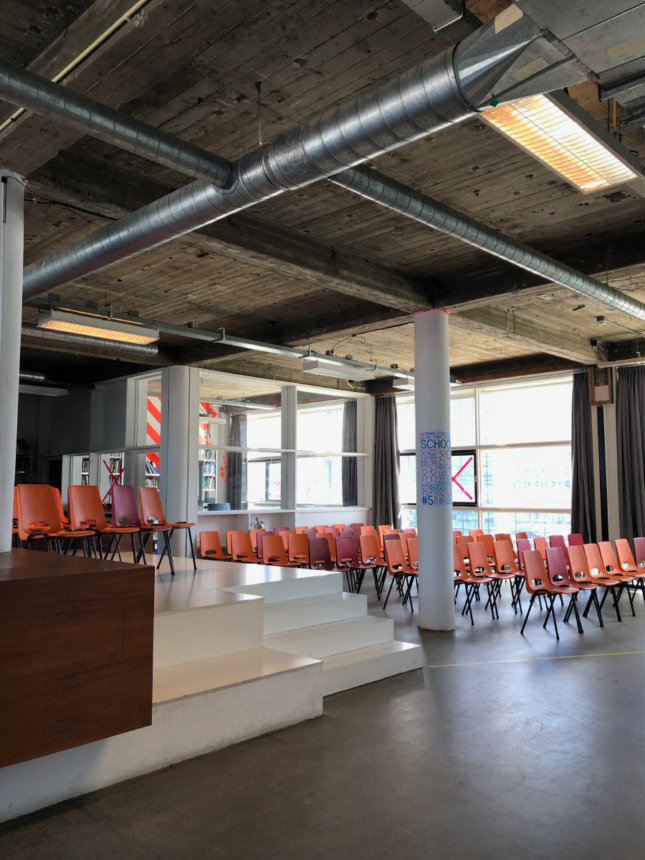 Interior photo of an industrial space with chairs and a bare ceiling