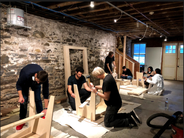 A group of students assembling furniture at the Kingston Creative Exchange, against a stone wall