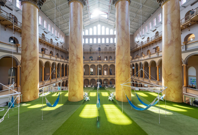 Image of sunlight streaming in through upper windows of the National Building Museum Great Hall, reflecting on fake grass of Lawn installation