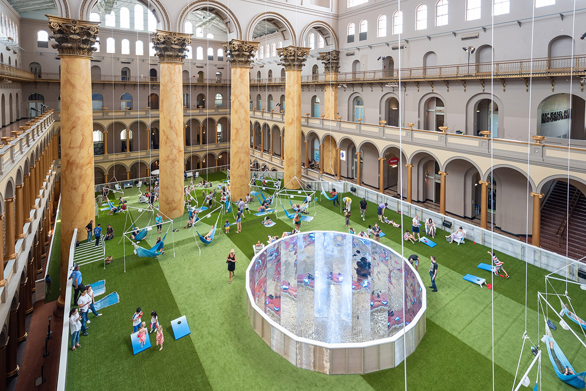 Aerial view of massive lobby of the National Building Museum with columns and green carpet laid out with people hanging out on blue hammocks and lawn chairs