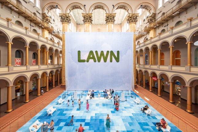 Photo of large white and blue sign with word LAWN printed on it and a blue checkered carpet below with people hanging around in the National Building Museum