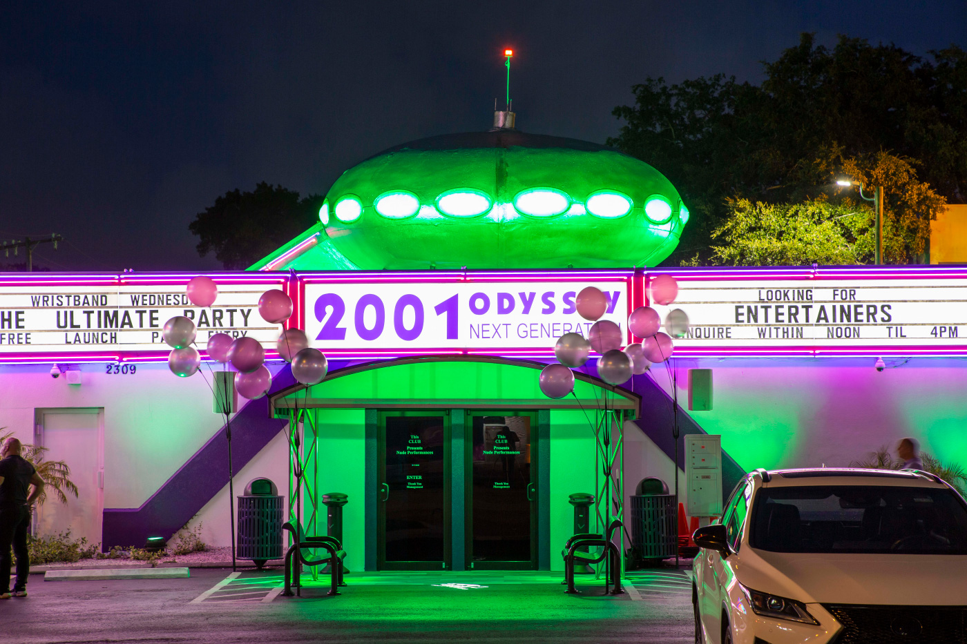 A strip club illuminated by green neon lights with a UFO-like Futuro house on top