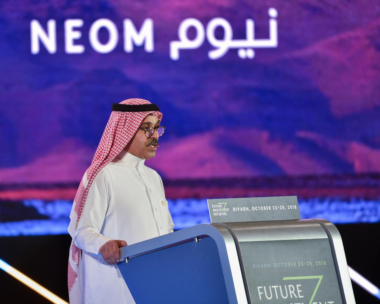 Image of man speaking at podium with purple sign behind him that says NEOM in English and Arabic