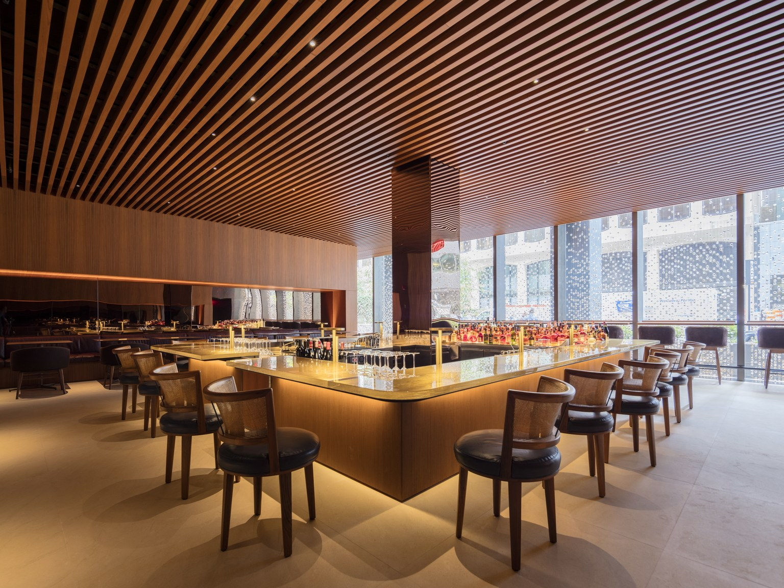 Interior of a warmly textured bar room with a wood ceiling, at the new Four Seasons