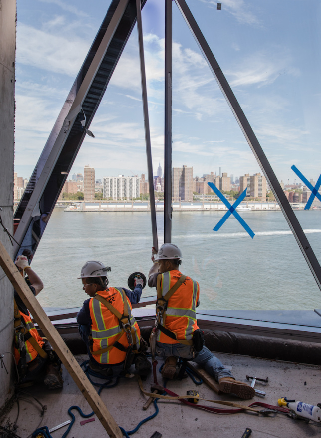 Installation image of workers installing glass panels at 10 Jay Street with Manhattan in the distance