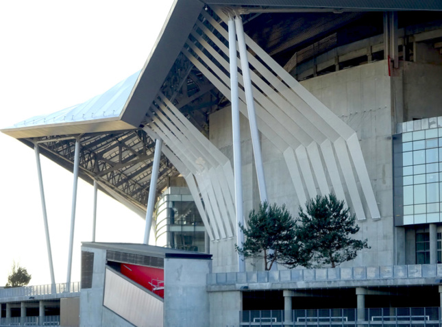 Side view of concrete arena with bracing that extends from wall to edge of canopy roof