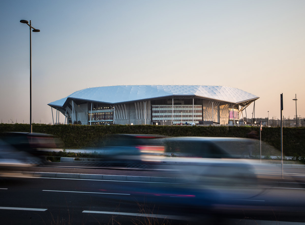 View from highway of white-capped World Cup stadium in twilight