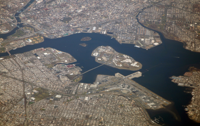 An aerial photo of Rikers Island, connected with a single bridge