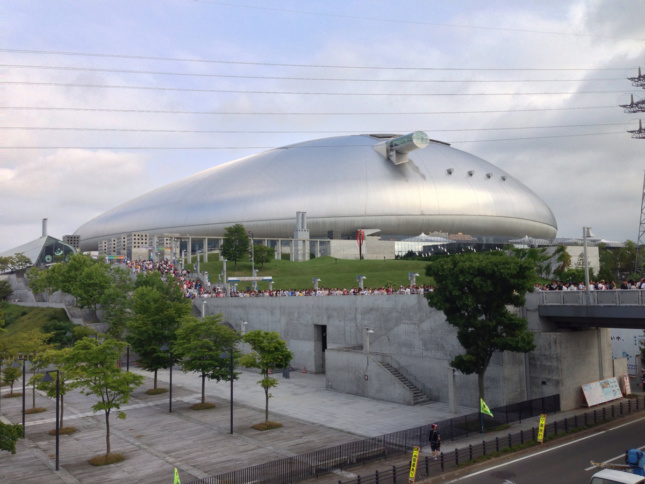 Silver pebble-shaped indoor arena outside near transit connection