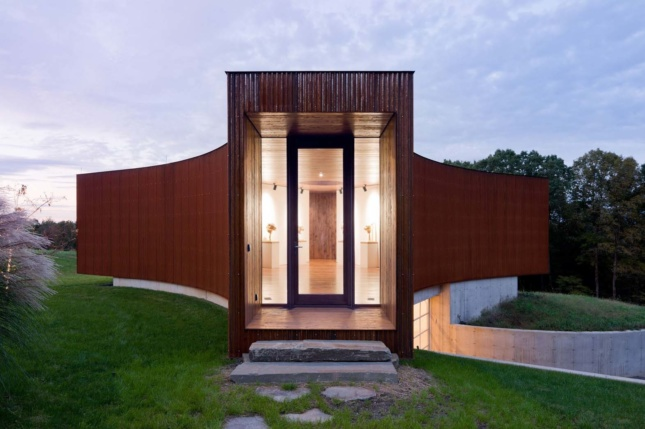 A guest house with large vertical entrance and weathered steel cladding