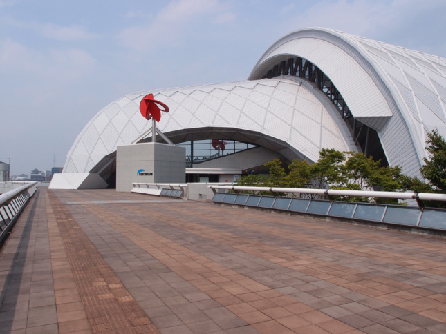 Exterior photo of walkway towards white curvy dome-like structure with swimming pool inside