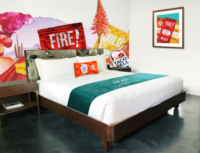 A taco bell themed hotel room with hot sauce shaped pillows and taco bell murals on the walls