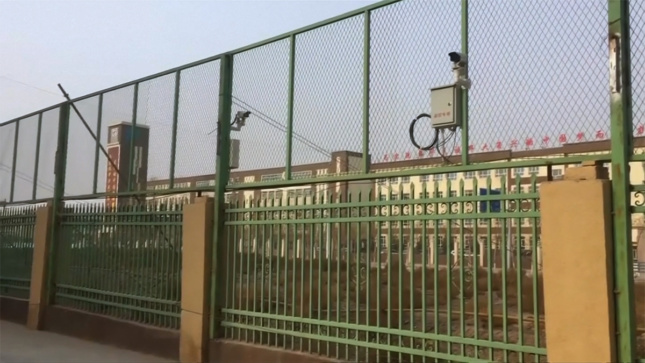 Screengrab from Vice News documentary showing Chinese detention center with green fence and high wire