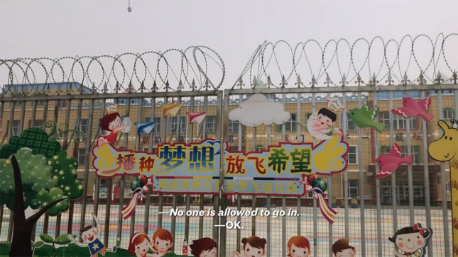 """Screen still from VICE News film showing barbed wire fence in front of yellow school for children. Text on screen says """"No one is allowed to go in."""""""
