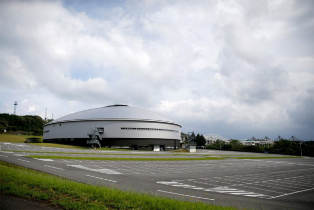 Exterior image of silver drum-like structure and parking lot