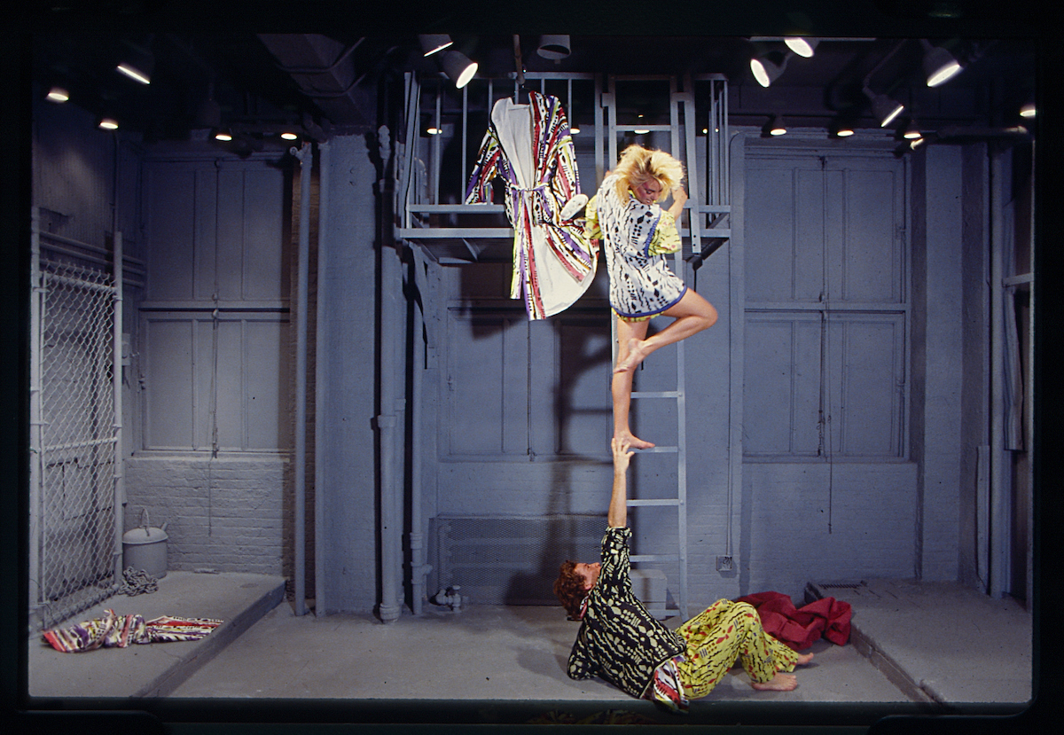 Long haired model on a ladder wearing bold printed tunic has their foot grabbed by model wearling yellow patterned pants and black and white patterned shirt, as part of a Willi Smith show